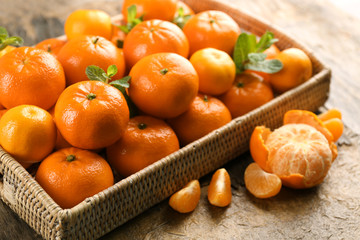 Full basket of fresh, delicious tangerines on the rustic table, close up
