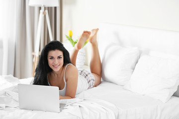 Beautiful happy woman in bed using laptop