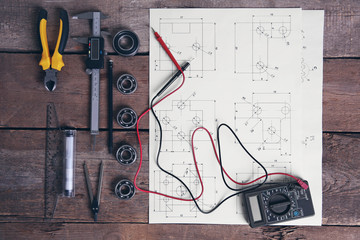 Digital multimeter and blueprint on a wooden background.