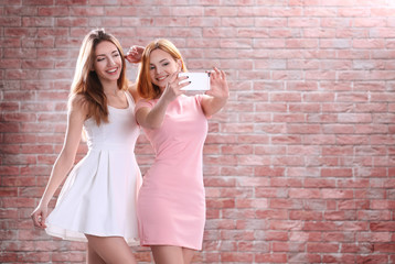 Young attractive girls taking selfie with mobile phone on brick wall background