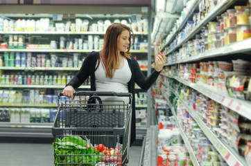 Pregnant woman choosing and buy food in supermarket