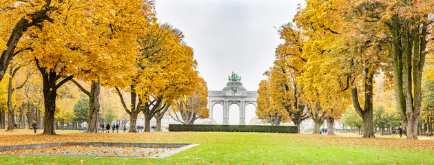 Fall trees in Parc du Cinquantenaire or Jubelpark is public park in Brussels, Belgium. The Triumphal Arch seen in background. Panoramic montage from 3 HDR images