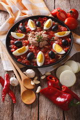 Tunisian tuna salad with grilled vegetables and ingredients close-up. vertical