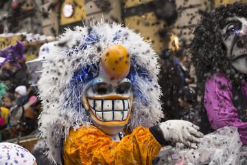 Ein Waggis mit gelb-weissem Kostüm wirft während der Basler Fasnacht 2016 Confetti in die Menge.