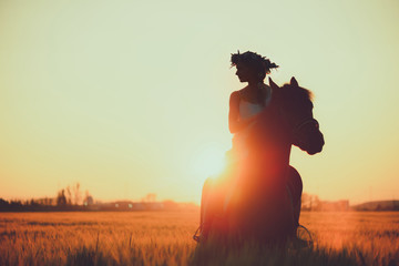 Girl with flowers wreathwhile riding horse at sunset