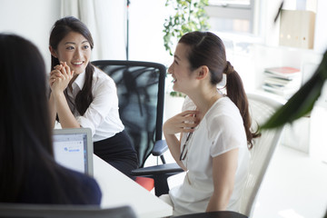 Three women have a planning meeting at the office