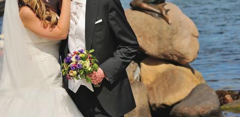 Happy young bride and groom together at coast in Copenhagen, Denmark
