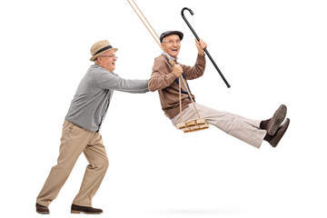 Two senior gentlemen swinging on a swing