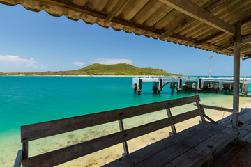 Emerald green water and blue sky with jetty, from inside the shelter