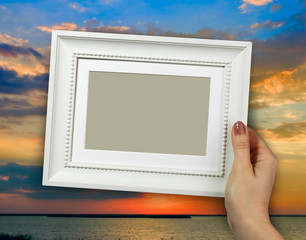 Wooden frame in woman hands on the background beautiful sunset