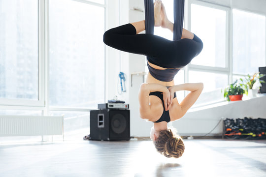 Attractive young woman doing aerial yoga