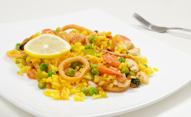 Paella with chicken and seafood on a white plate, close-up, side view