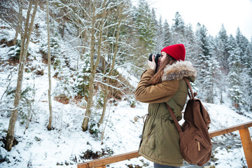 Concenrated woman photographer standing and taking pictures in mountains