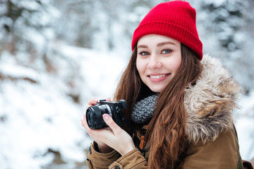 Happy beautiful woman photograher taking photos in winter forest