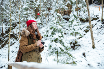 Smiling inspired woman photographer taking photos at forest in winter