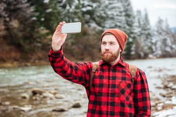 Male hiker making photo on smartphone
