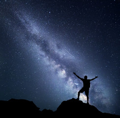Landscape with Milky Way. Night sky with stars and silhouette of a happy climber with backpack and raised up arms on the mountain. Space background