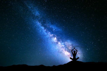 Landscape with blue Milky Way. Night sky with stars and silhouette of a girl practicing yoga in the hill.