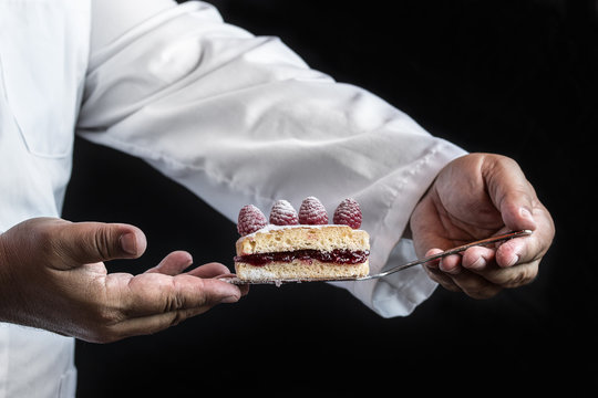 Chef man hands with a cake over black background, close up detai