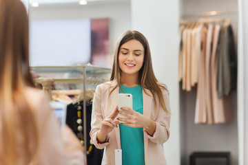 woman taking mirror selfie by smartphone at store