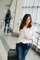 young woman with dark hair in a white blouse goes with a suitcase holding a map at the train station.