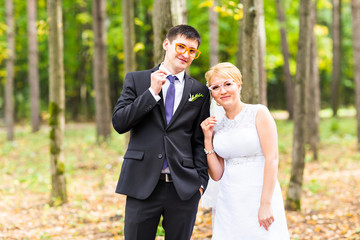 April Fools' Day. Wedding couple posing with stick lips, mask.