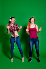 Two young women having fun, listening to music with headphones