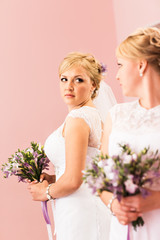 beautiful bride girl  with hairstyle and bright makeup looks in the mirror
