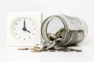 Close up coins in jar with table clock at side represent time is money.