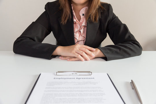 Businesswoman sitting with employment agreement in front of her