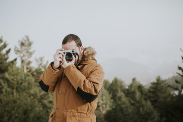 Man taking a picture with his camera while standing outdoors