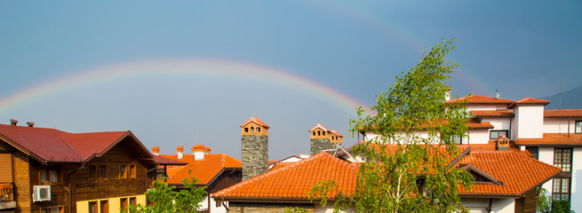 Panorama background with Rainbow over red roofs of the houses