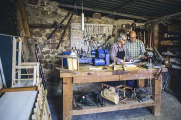 Elderly woman and man working in his workshop