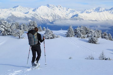 Fotomurales - Female hiker on snowshoes in the snow covered mountains in France during a microadventure.