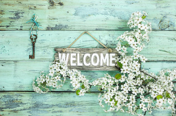Welcome sign hanging by skeleton key and spring flowers
