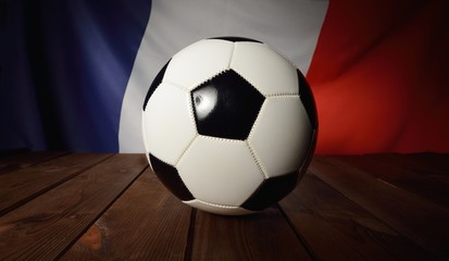 Flag of France with football on wooden boards as the background.
