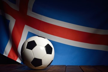 Flag of Iceland with football on wooden boards as the background.