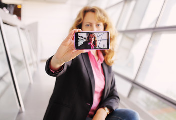 Beautiful businesswoman taking selfy picture on mobile device