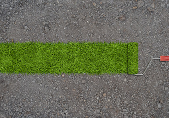 Strip of green grass made by roller for painting on a ground with small stones.