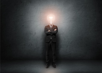 Businessman with light bulb instead of head on concrete room