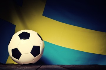 Flag of Sweden with football on wooden boards as the background. Vintage Style.