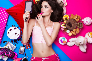 Beautiful fresh girl doll lying on bright backgrounds surrounded by sweets, cosmetics and gifts. Fashion beauty style.