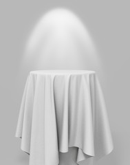 white cloth on a round pedestal on a gray background with illumi