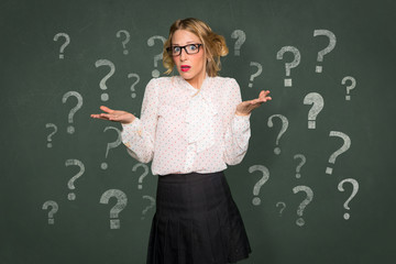 Teacher professor woman without answers surrounded by question mark blackboard chalk confusion