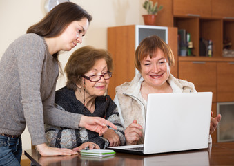 pensioners and relative working on laptop