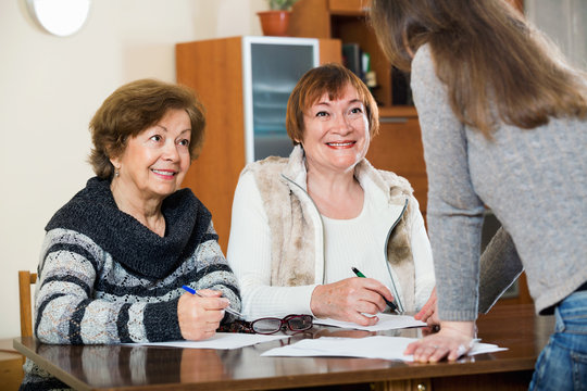 Elderly cute positive women making will at public notary office