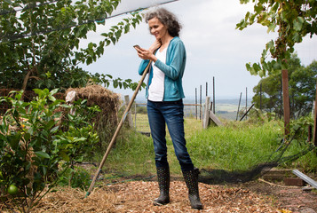 Mature woman with grey hair and jeans, in large garden leaning on rake handle and smiling at smart phone