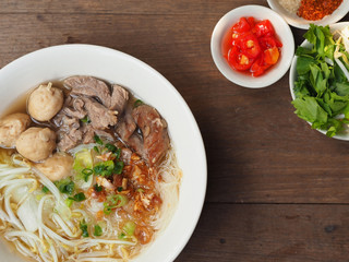 asian noodle soup with pork meatball with fresh vegetable on wood table vintage style, simply food, street food, hot and spicy noodle soup, asian food