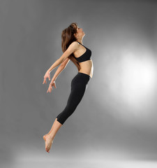 Young sporty woman jumping on grey background