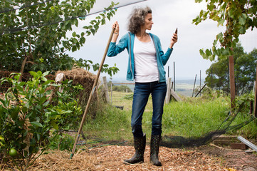 Profile of mature woman in blue top and jeans in large garden, leaning on rake handle and using smart phone